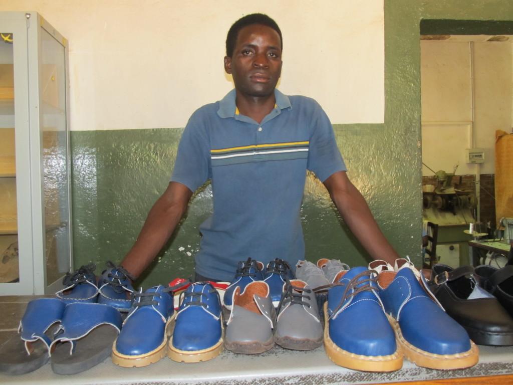 Chimwemwe mwenyemasi poising with his handmade shoes