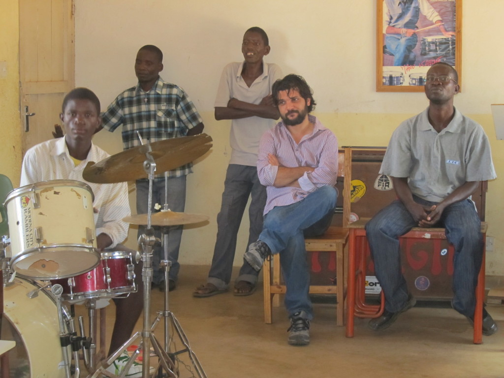 Alessandro and Thom Damba (Right) watch while Andiamo music school students perform during their training