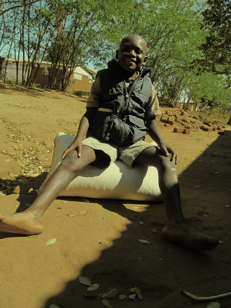 Martin Masauko sitting on his Bag of Maize