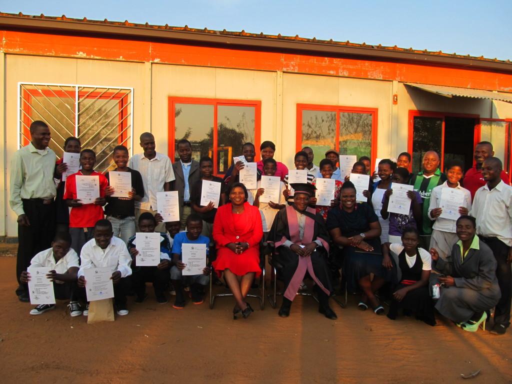 Group photo: Mpetiwa, Murowa, AEI staff members posing with the graduating team