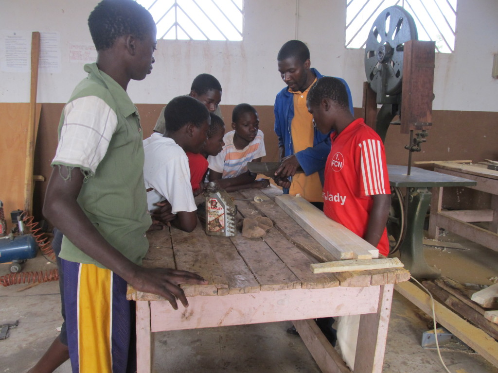 Mr. July teaching the trainees some skills in planing