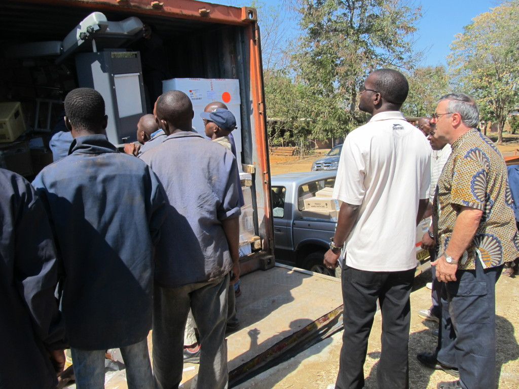Mr. P. Bwanali and Fr. Mario watch while offloading