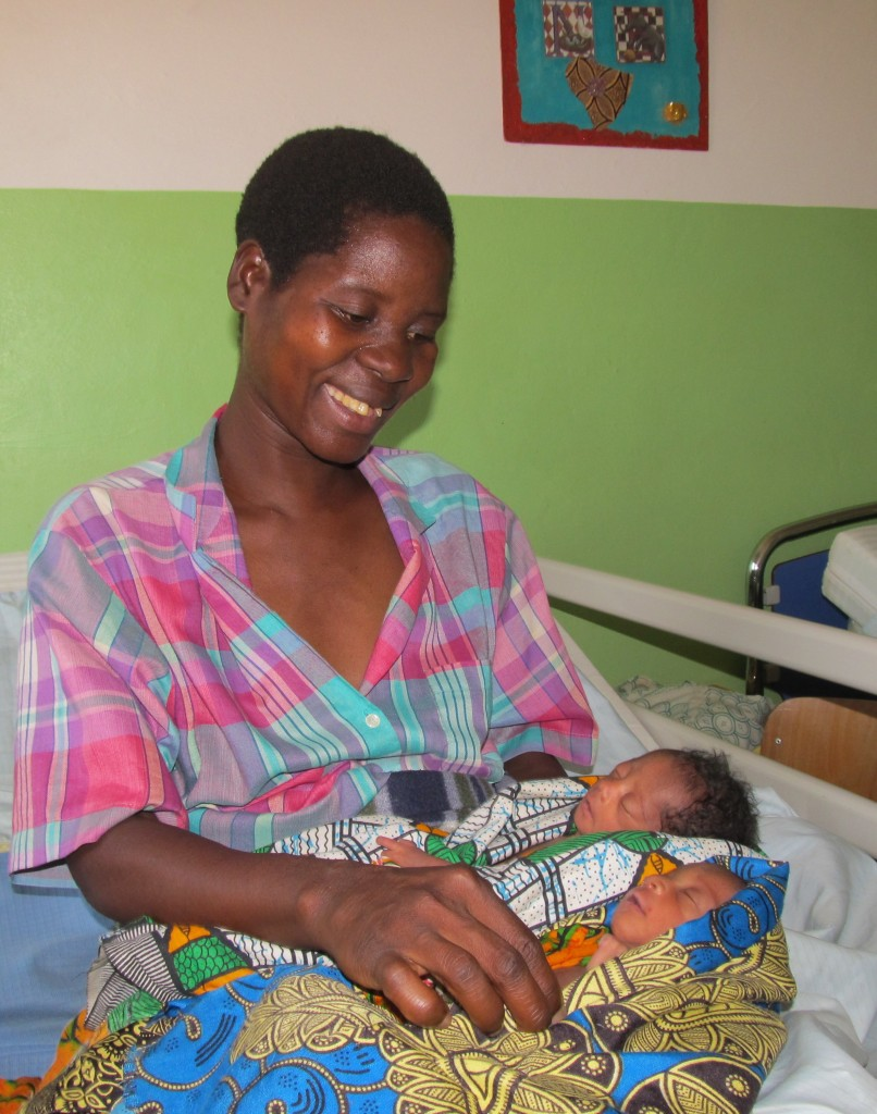 Eliza smiling at her twins in Comfort Community Hospital Neonatal ward