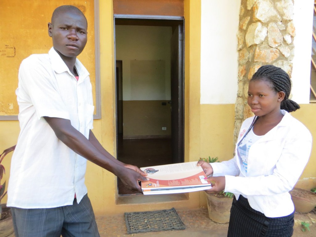 AEI Bursar, Fanny Bentala giving exercise books to Kisimu