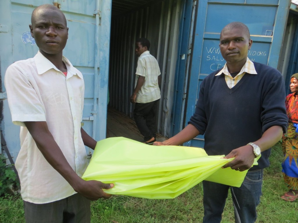 Kasimu receives the plastic paper from Goster at AYCT